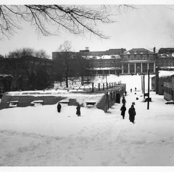 Winter view of quonset huts used for temporary classrooms after World War II, located between Peele Hall and 1911 Building (in background), North Carolina State College, February 1948.