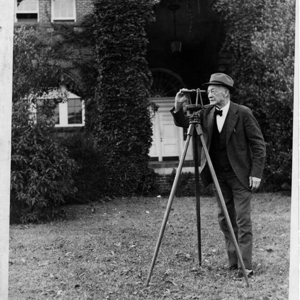 W. C. Riddick poses with with surveying instrument used in the late 1830s to survey the right-of-way for the Raleigh and Gaston Railroad.