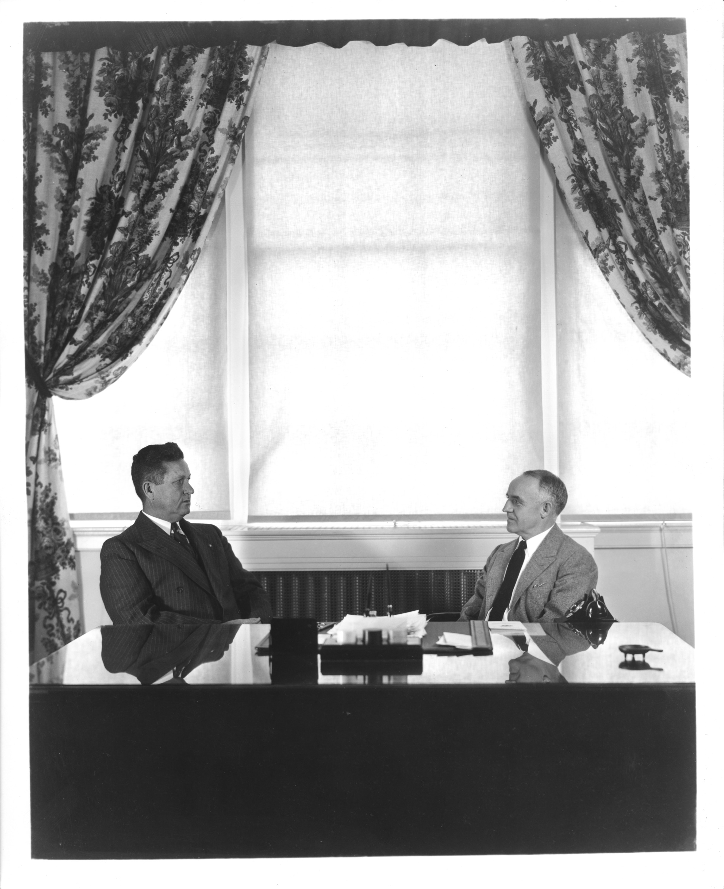 Dean of Administration at North Carolina State College, John William Harrelson, and President of the Consolidated University of North Carolina, Frank Porter Graham, seated left to right at desk.