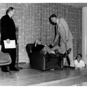 Edward L. Cloyd, retired dean of students, leaning back in reclining chair on stage