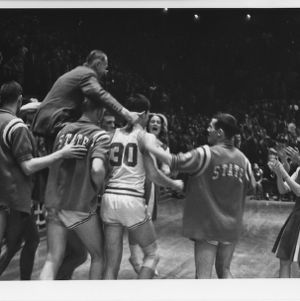 NC State College basketball players carry Coach Everett Case around court on his last game