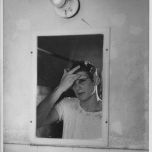 View of North Carolina State College all-American basketball player Sam Ranzino's reflection in locker room mirror.