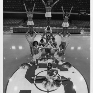 North Carolina State University cheerleaders posing at center court in Reynolds Coliseum.