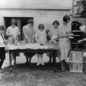 Home demonstration agent Rosalind Redfearn giving a bread-making demonstration to a group of girls and boys on the lawn of Anson County Courthouse, North Carolina.