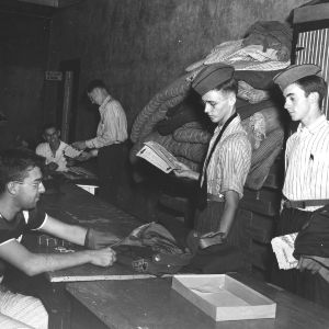 Arnold Krochmal seated in the Military Store distributing ROTC uniforms to freshmen students