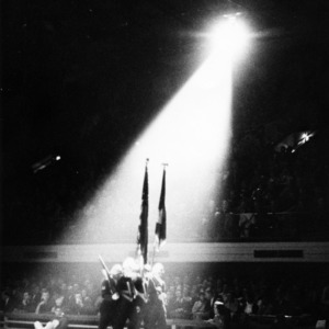 Flag bearers marching inside gymnasium