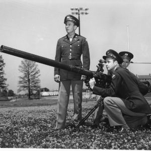 A recoilless rifle claims the attention of three North Carolina State College ROTC cadets