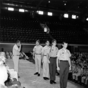 Cadets stand at attention before an officer