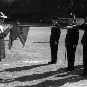 Female cadet prepares company flag for presentation