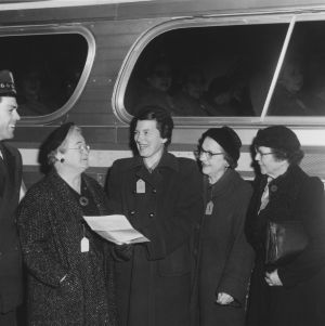 Bus driver and four women standing next to bus