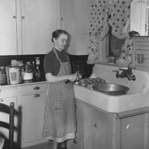 Mrs. Fred Christian, of Stokes County, peels potatoes in a model kitchen