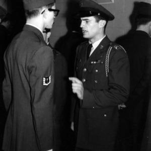 Military officer inspecting cadet