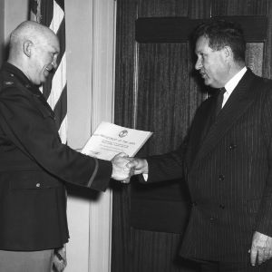 "U.S. Army officer presenting certificate to Chancellor John W. Harrelson in recognition of ""proficiency in the training of the Reserve Officers' Training Corp"""