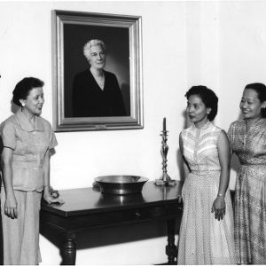 Ruth Current with foreign visitors in front of portrait of Mrs. Jane S. McKimmon