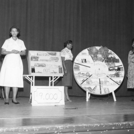 Four women standing on a stage with displays of food and marketing