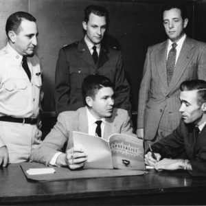 David B. Stansel holding a military specialist training manual while at table with others