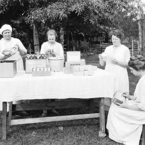 Home Demonstration club members grade and pack poultry and other products for sale by parcel post and express shipments