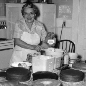 Interior view of woman using hand mixer in kitchen, with cakes in foreground