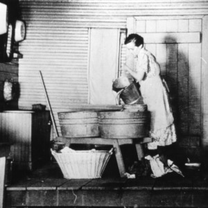 Woman pouring water in a wash tub, preparing to do laundry