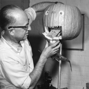 Man demonstrating a jaw mechanism for a carved pumpkin