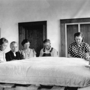 Group of women and one man sewing a mattress together, 1940-1941