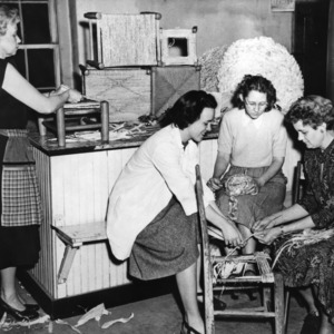 Four women reweaving chair seats