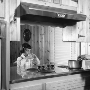 Woman and a young girl standing in a kitchen
