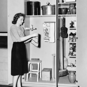 Woman hanging a dish towel in a kitchen pantry