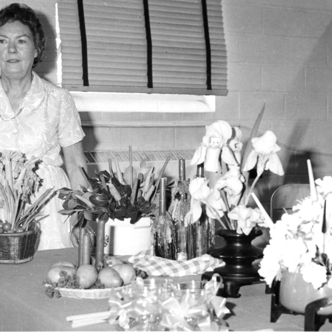 Ann Williamson, Columbus County club chairman, with flower arrangements.