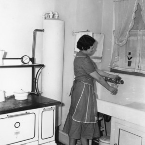 Mrs. E. L. Minor, the first winner of the county kitchen contest in 1937-1938 standing in front of a sink