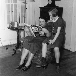Mrs. George R. Bockwell and her daughter Ruth participating in the House Furnishings Project, demonstrating a well-lighted living room