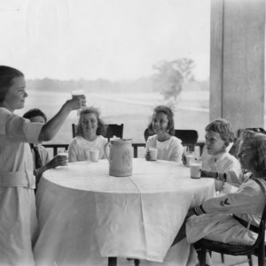 Six children around a table with glasses of milk, while one of them makes a toast