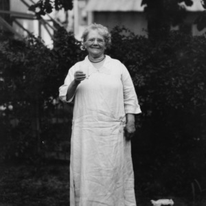 Woman standing in yard holding a glass of milk