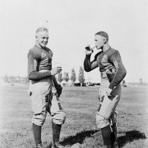 Two football players on field, drinking glasses of milk