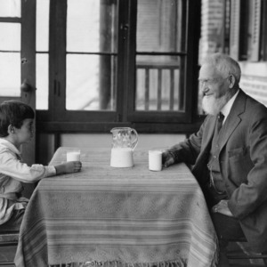 Young boy and elderly man sitting at table facing one another, with a pitcher of milk between them and glasses of milk in front of them