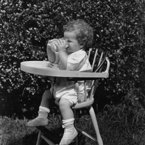 Child in highchair drinking milk