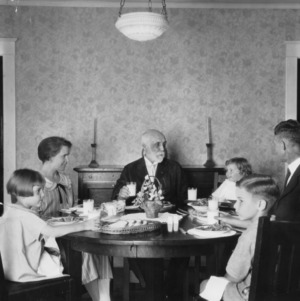 Family sitting at table, eating dinner and drinking milk
