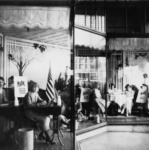 Women posing in storefront window to advertise drinking milk in the school room, on a picnic, and at a party