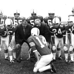 Wally Ausley and Bill Jackson huddling with N.C. State players
