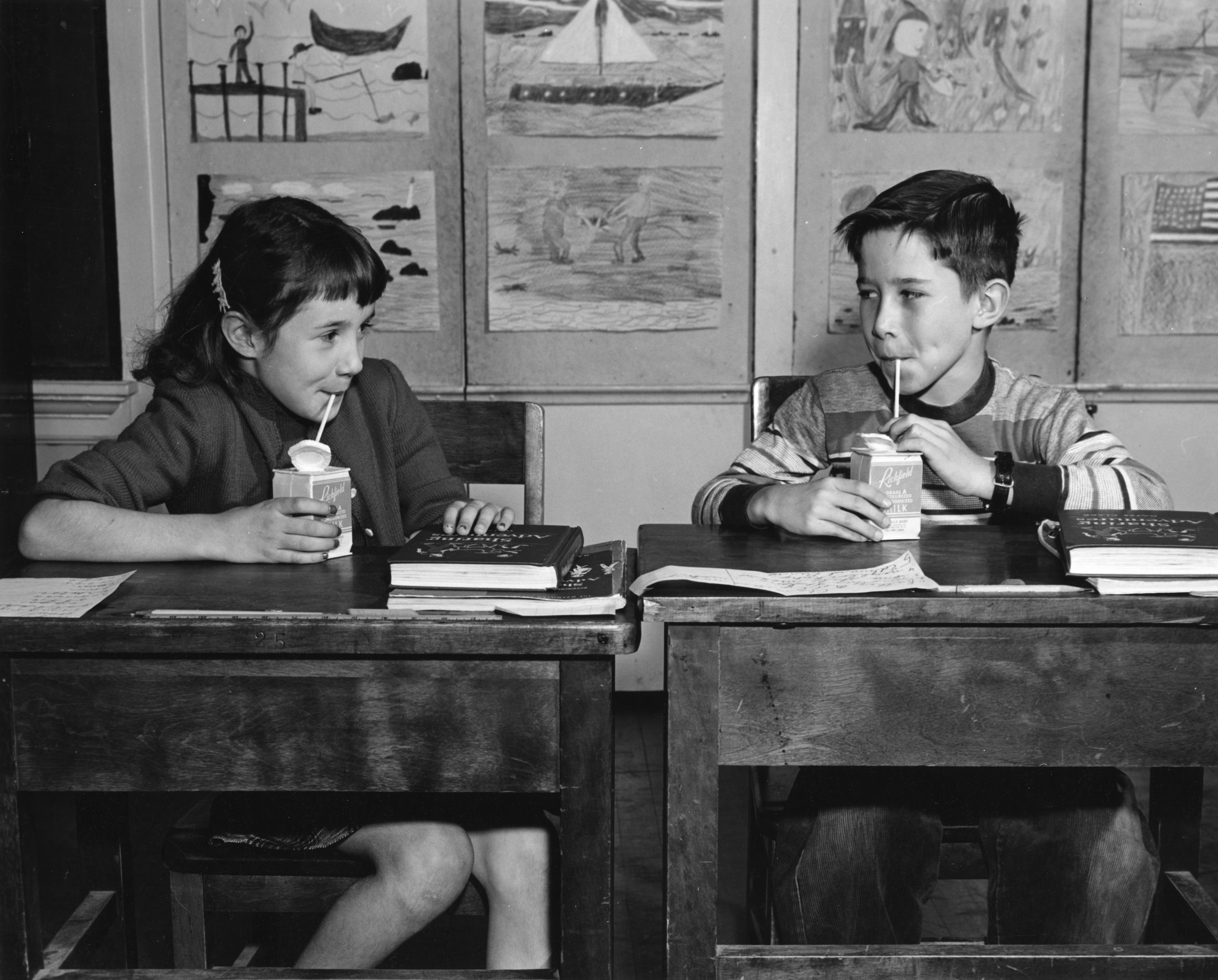 Young girl and young boy sitting at desks looking at one another while drinking from cartons of milk