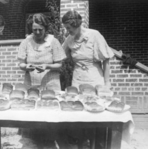 Exterior view of three women inspecting bread loaves while a fourth looks on