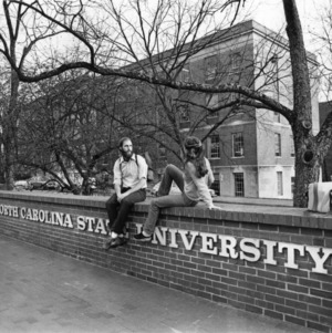 Two students sitting on brick wall in front of Nelson Hall, North Carolina State University.