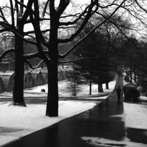 Man walking on path beside quonset huts on the North Carolina State College campus during winter.