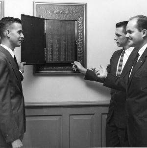 Alumni Association president Richard L. Rice and two students looking at plaque for Alumni Memorial Building