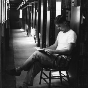 Student reading in stacks of D. H. Hill Library, North Carolina State College