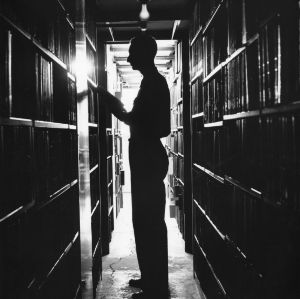 Silhouette of man standing with book in D. H. Hill Library stacks.