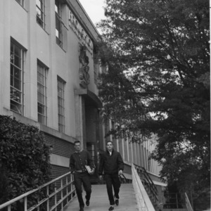 Two students walking down ramp in front of Broughton Hall, North Carolina State College