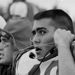 North Carolina State College quarterback Roman Gabriel on the sidelines with headset during football game against University of Wyoming.