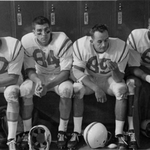 Four North Carolina State College football players sitting in locker room at halftime during University of Wyoming game.