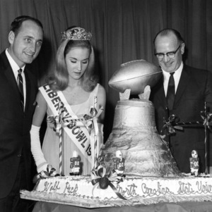 """Miss Liberty Bowl"" Nancy Brackhan, North Carolina State University football coach Earle Edwards, and University of Georgia football coach Vince Dooley posing at the 1967 Liberty Bowl awards banquet"
